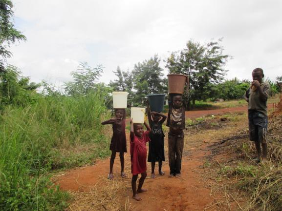 Children carry buckets in rural Ghana.
