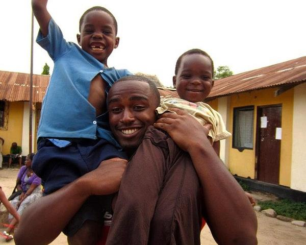 Man holding 2 children on shoulders
