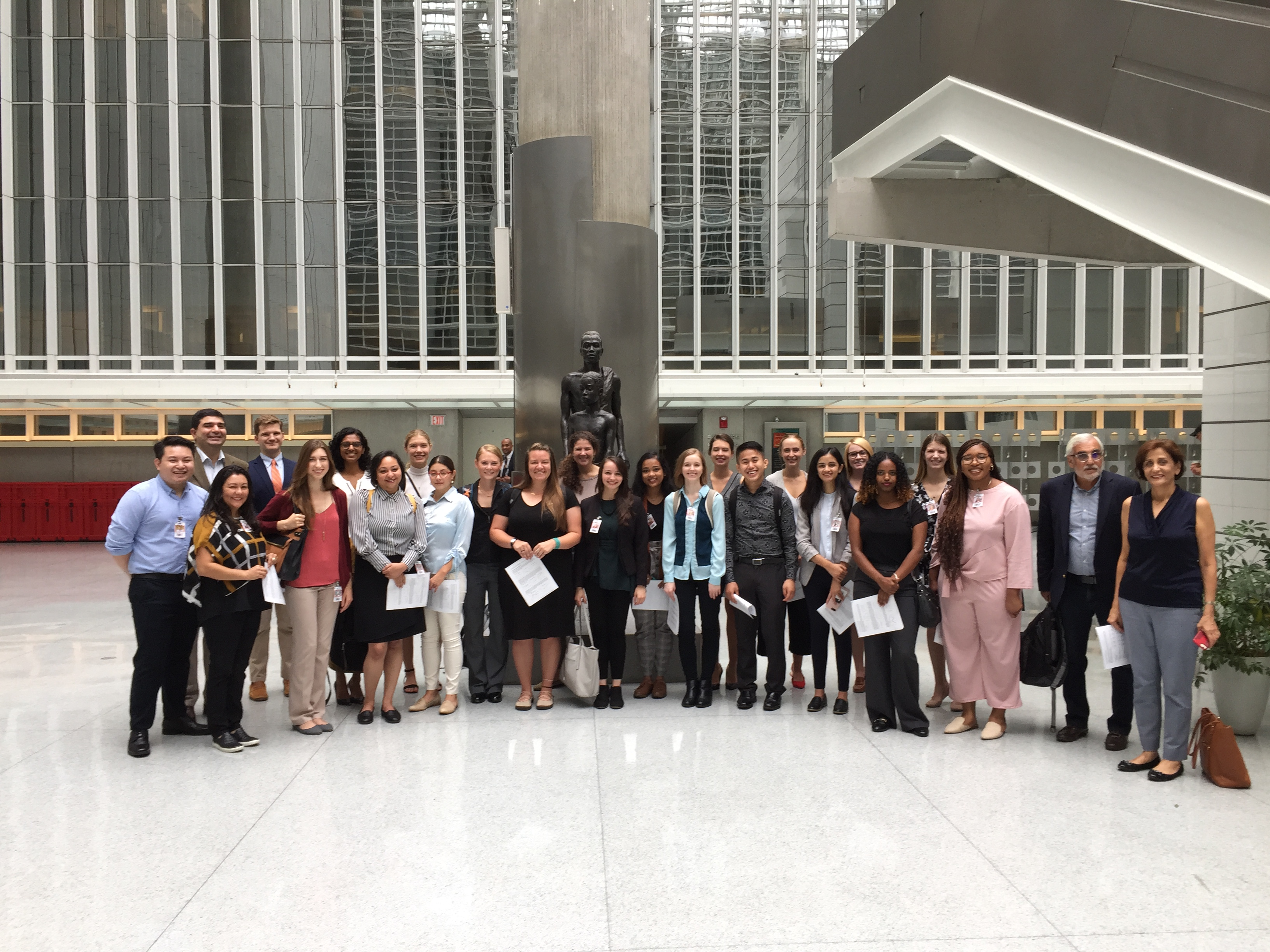 Students and faculty pose in the atrium of the World Bank building.
