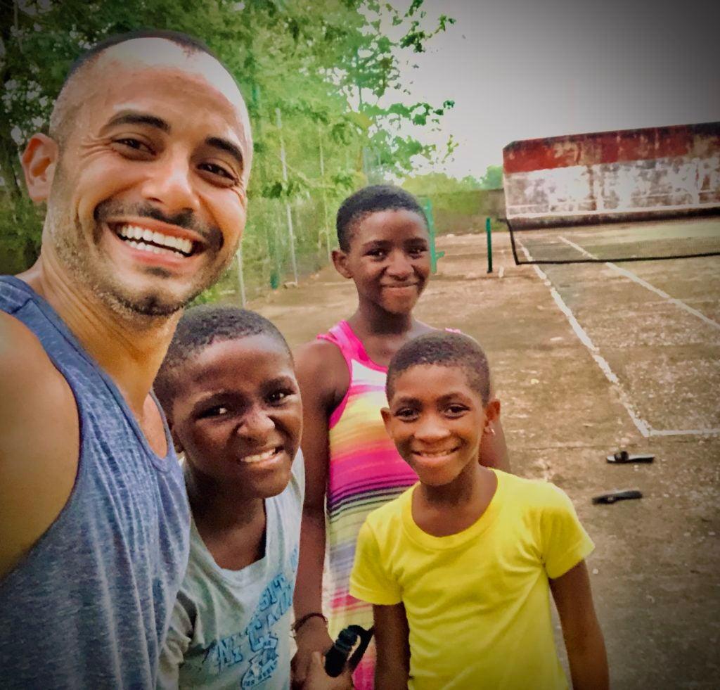 Marco Martinez with children in Navrongo, Ghana on a tennis court.